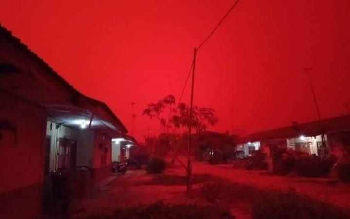 Mała uliczka w wiosce, werandy domów oświetlone niebieskim światłem żarówek, w tle krwistoczerwone niebo skryte pod warstwą pyłu