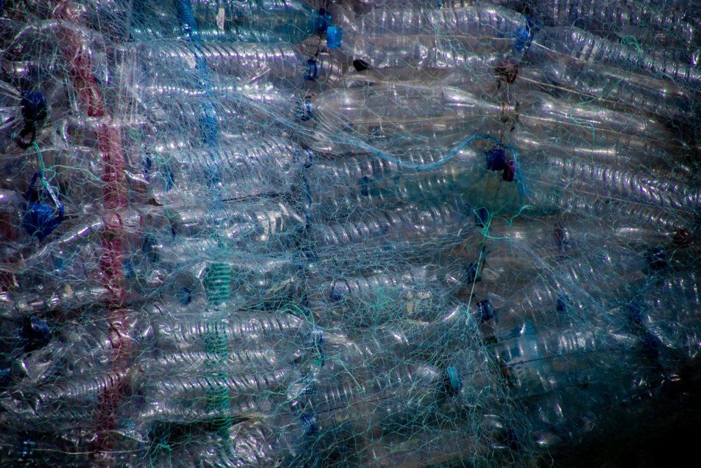 Puste, niebieskie, plastikowe butelki po wodzie mineralnej zawinięte w sieć rybacką.