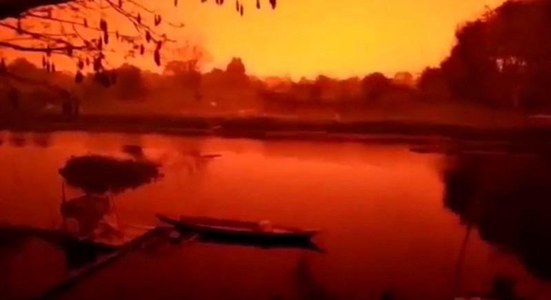 Zdjęcie przeciwległego brzegu rzeki, słońce schowane za warstwą pyłu, wszystko w nierealnej czerwonej barwie