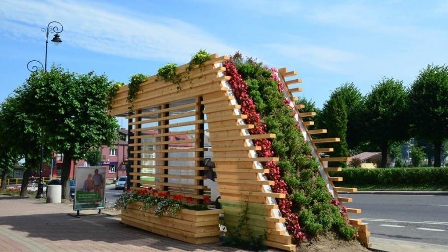 drewniana wiata przytsankowa pokryta sadzonkami kwiatów, oraz pnączami