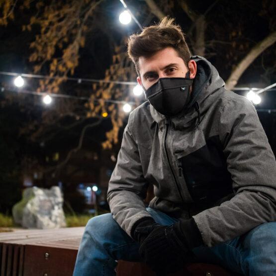 mężczyzna w czarnej maseczce ochronnej wielorazowej siedzi na ławce